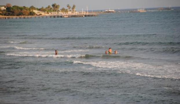 Sidede turistler denize giriyor